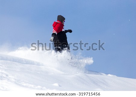 Jumping snowboarder from hill in winter #319715456