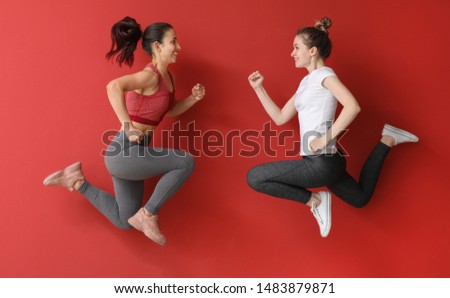 Jumping sporty women on color background