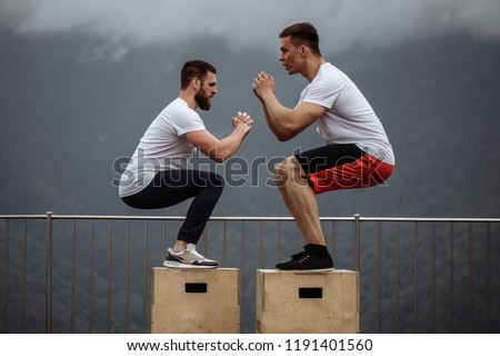 Jumping squats exercise - young handsome caucasian athletes doing functional outdoor workout in mountain area, training physical endurance and strength. #1191401560