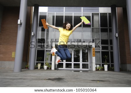 Jumping student girl at campus - stock photo