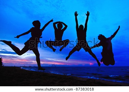 jumping team at sunset time as silouette background