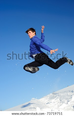 Jumping teenager in a cold day on snow field