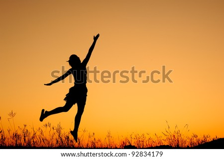 Jumping woman and sunset silhouett