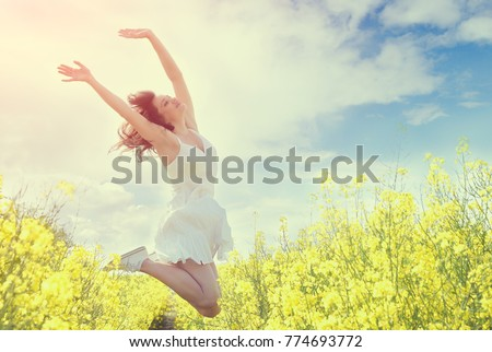 Photo of Jumping Woman in yellow field. Toned image