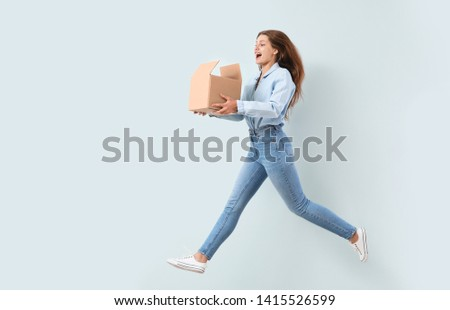 Jumping woman with cardboard box on light background
