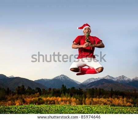 Jumping yoga by Indian man in padmasana lotus pose with Christmas tree in white trousers, red socks and Christmas hat at mountain background. Free space for text
