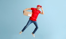 Jumping young male courier with box on grey background