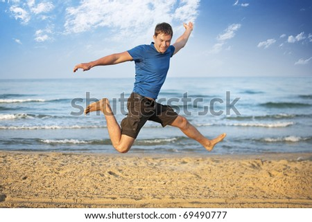 Jumping young man in the sand against the sea