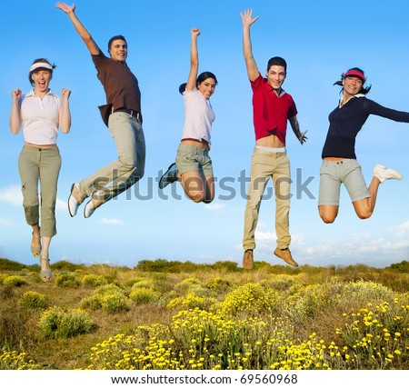 Jumping young people happy group in yellow flowers field [Photo Illustration]