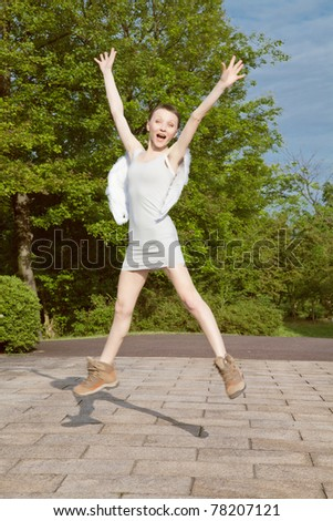 Jumping young woman wearing wings