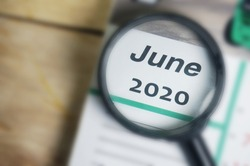 June 2020 Calender under magnifying glass. Selective focus.