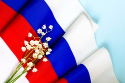 June 12 - Independence Day of Russia. Postcard for the holiday Day of Russia. A bouquet of lilies of the valley against the background of the Russian flag. Scarf in the colors of the Russian flag.