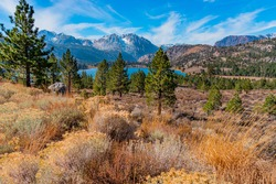 June Lake sits in the valley of the Californian Sierra Nevada mountains, on the June Lake Loop in Central California. The fall trees line the lake in the distance.