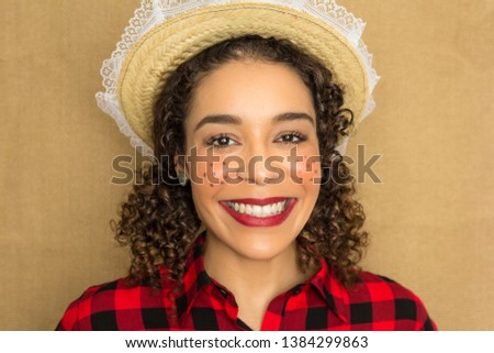 June Party or Festa Junina in Brazil. Pretty woman is having a big smile and looking at the camera. She wears red and black plaid shirt. The girl is wearing a straw hat. #1384299863