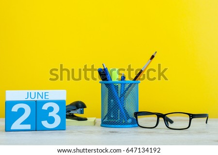 June 23rd. Day 23 of month, calendar on yellow background with office suplies. Summer time at work. International Olympic Day