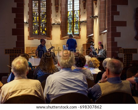 June 24, 2017. Senior citizens listen to and sing along with a church orchestra in Old St Nicholas Church, Romerberg, Frankfurt, Germany. Travel and religion editorial concept.