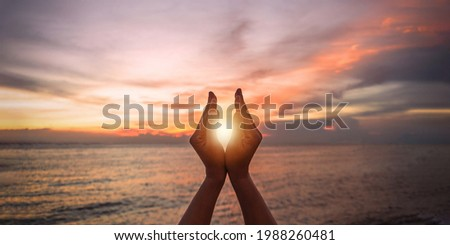 June summer sun solstice concept with silhouette of young woman's hands relaxing, happy meditating and holding sunset against warm golden hour sky on the beach with natural ocean or sea background Foto d'archivio ©