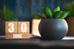 june 30th. Day 30 of month,  Cube calendar with date and pot with succulent placed on table at home Simple calendar. summer month, day of the year concept.