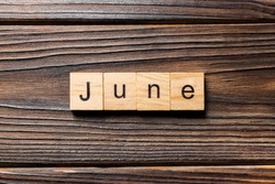 June word written on wood block. June text on wooden table for your desing, Top view concept.