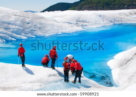JUNEAU, ALASKA - JUNE 3:  Unidentified hikers take a rest at one of the many pools of blue water on top of Mendenhall Glacier on June 3, 2009 in Juneau, Alaska.