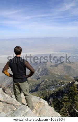 Junger Wanderermann, der die atemberaubende Ansicht auf Gipfelerwägt. Erstaunliche Ansicht des Joshua Baum-Nationalparks und derPalme entspringt, KALIFORNIEN. - stock photo