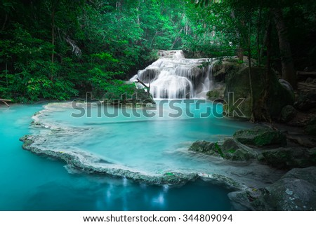 Jungle landscape with flowing turquoise water of Erawan cascade waterfall at deep tropical rain forest. National Park Kanchanaburi, Thailand stock photo