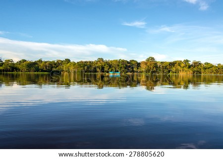 Jungle sky and boat reflected in the clear blue water of the Javari River in the Brazilian Amazon Rainforest