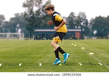 Junior football club player training on soccer ladder. Football training for sport team. Young boy runnong on agility ladder. Football training equipment: ladder, goal and cones Stock photo ©