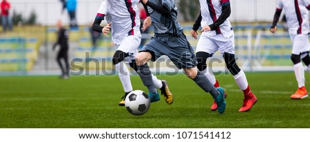 Junior Football Match. Soccer Game For Youth Players. Boys Playing Soccer Match on Football Pitch. Football Stadium and Grassy Field in the Background