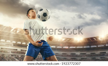 Junior football or soccer player at stadium in flashlight. Young male sportive model training. Moment of attacking, catching. Concept of sport, competition, winning, action, motion, overcoming.
