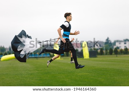 Junior Football Player Running with Parachute. Soccer Endurance and Strength Training. Player Speed Testing. Professional Soccer Strength Test. Young Boy in Football Club Exercise on Training Venue