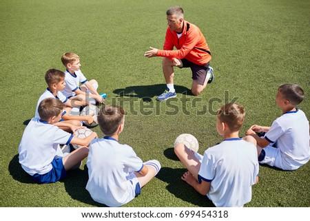 Junior football team sitting around coach listening to lecture in field #699454318