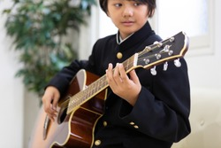 Junior high school student playing the guitar
