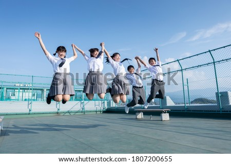 Junior high school students jumping on the roof Stock photo ©