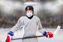 Junior ice hockey player with full equipment and sports uniform posing in arena with face mask. Concept of new normal in sports to prevent Covid-19 coronavirus spread when sports leagues resume.