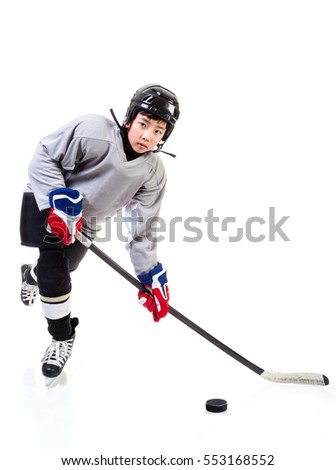 Junior ice hockey player with full equipment and uniform posing for a shot with a puck. Isolated on white background.
