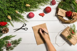 Juniper branches with a Christmas decor. Christmas, New Year background. Coniferous branches of juniper, a sheet of kraft paper and a pen.