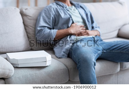 Junk Food And Gastritis. Unrecognizable African Man Having Stomachache After Eating Spoiled Pizza Touching Aching Abdomen Sitting On Sofa At Home. Food Poisoning. Cropped, Selective Focus On Pizza Box Stok fotoğraf ©
