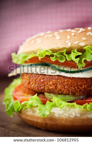 Junk food hamburger concept. Deep fried chicken or fish burger sandwich with lettuce, tomato, cheese and cucumber on wooden background.