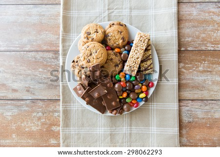 junk food, sweets and unhealthy eating concept - close up of candies, chocolate, muesli and cookies on plate #298062293