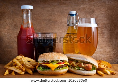 Junk food with burger, hotdog, french fries, cola, ketchup and beer on a wooden background