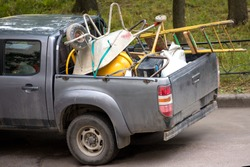 Junk in the cargo area of a passenger truck. Trolley and ladder. Rear end car