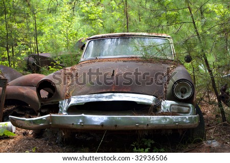 Junk yard vehicles showing old rusted car in overgrown weedy area