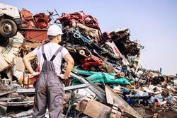 Junkyard worker looking at large pile of scrap metal.
