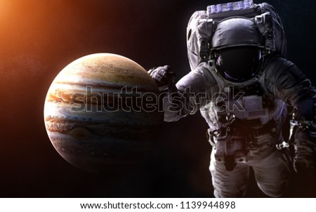Stock Photo Jupiter on a blurred background with a giant astronaut. Image in 5K resolution for desktop wallpaper. Elements of the image are furnished by NASA