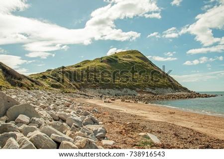 Jurassic coast beach in the summertime. A beautiful summertime beach scene along the Jurassic coast of Dorset, United Kingdom. #738916543