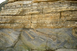Jurassic sandstones have overlain mudstones in an unconformity in strata exposed along the Dinosaur Coast. Tilting of the older strata and the subsequent layering of the sandstone creates this feature