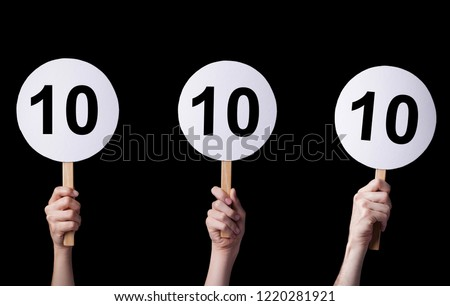 Jury members\' hands showing a perfect score