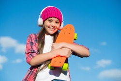 Just a little more plastic underfoot. Happy skater on blue sky. Small kid hold penny board. Riding penny skateboard. Speed and balance. Summer vacation and holidays. Penny board for beginner.