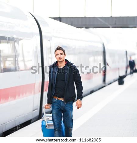 Just arrived: handsome young man walking along a platform at a modern train station
